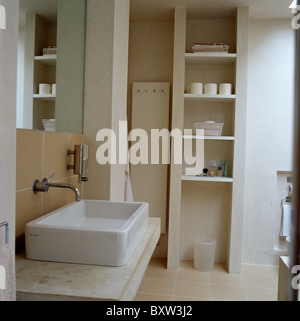 Rectangular white basin on polished concrete vanity unit in modern bathroom with open shelving - Stock Photo