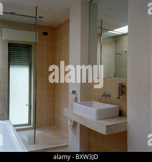 Mirror above rectangular basin on polished concrete vanity unit in modern tiled bathroom with walk-in shower - Stock Photo