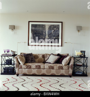 Large black+white picture above patterned beige sofa in modern living room with swirly-patterned beige carpet