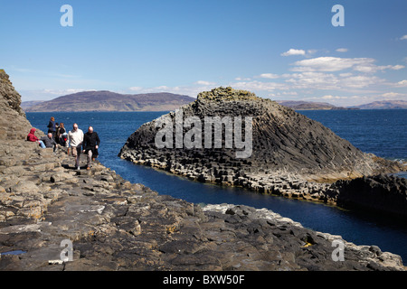 Tourists and Polygonal basalt, Am Buachaille rocks, Staffa, off Isle of Mull (in distance), Scotland, United Kingdom - Stock Photo
