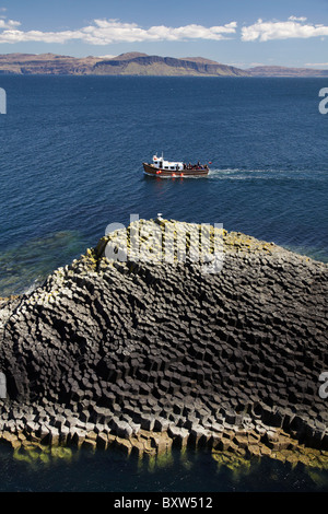 Staffa tour boat and polygonal basalt, Am Buachaille rocks, Staffa, off Isle of Mull (in distance), Scotland, United - Stock Photo