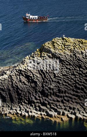 Staffa tour boat and polygonal basalt, Am Buachaille rocks, Staffa, off Isle of Mull, Scotland, United Kingdom - Stock Photo