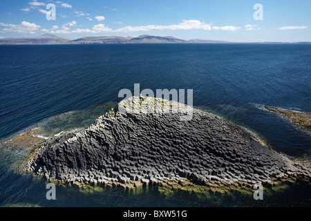 Polygonal basalt, Am Buachaille rocks, Staffa, off Isle of Mull (in distance), Scotland, United Kingdom - Stock Photo