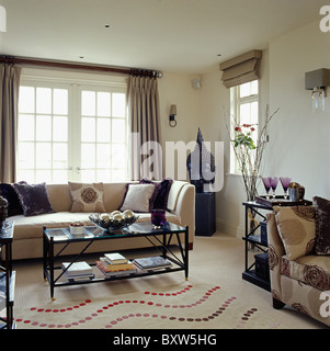Cream living room with cream table and sofas and gold accessories ...