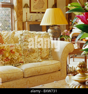 Cream lamp on table beside cream sofa with cream tapestry cushions in country living room - Stock Photo