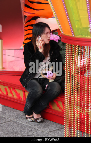 chinese woman talking deperately in mobile phone during chinese new year - Stock Photo