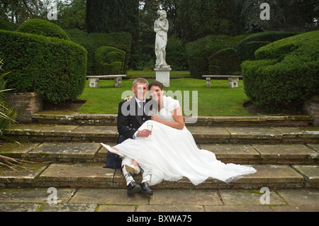 Horizontal portrait of a bride and groom having some quiet time together in an ornamental garden on their wedding - Stock Photo