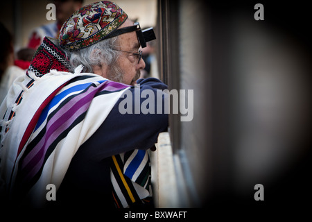 Jewish man with traditional Talit prayer shawl and Tefillin phylacteries at Western Wall in Jerusalem - Stock Photo