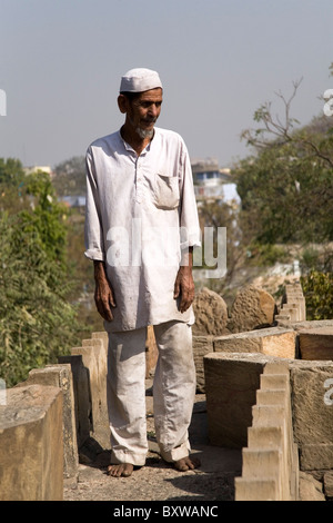 A Muslim man stands on the roof of the Bai Harir Mosque at Ahmedabad, Gujarat, India. - Stock Photo