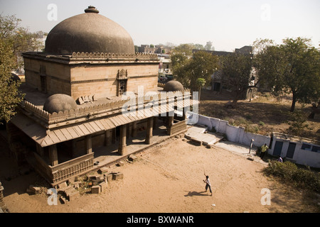 A child plays in the dusty courtyard of the Bai Harir Mosque at Ahmedabad, Gujarat, India. - Stock Photo