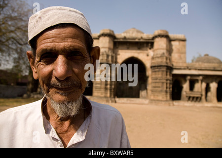 A Muslim man in a prayer cap stands in front of the Bai Harir Mosque at Ahmedabad, Gujarat, India. - Stock Photo
