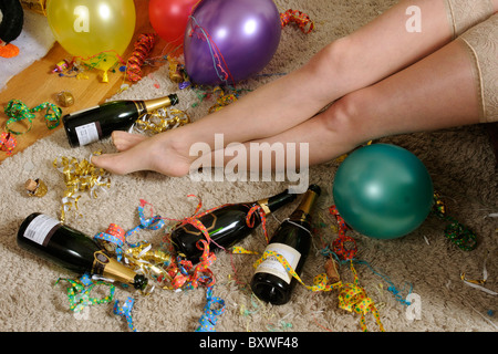Woman laying on the floor & suffering a hangover Christmas new year parties - Stock Photo