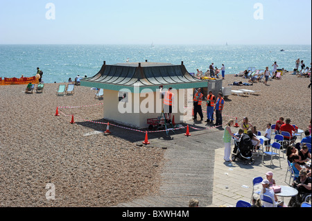 Young offenders painting a small hut on Brighton beach as part of the community Payback scheme - Stock Photo