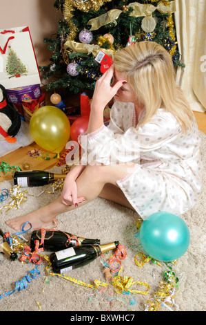 Female party goer wearing a dressing gown with hand over her forehead suffering with headache - Stock Photo