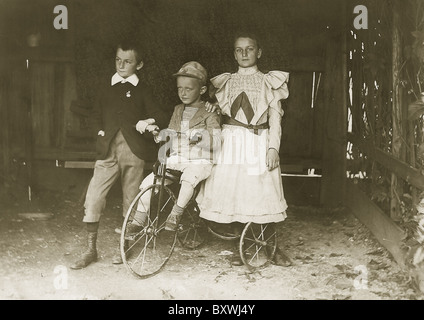 Three siblings share a bike. circa: 1900-1910 - Stock Photo