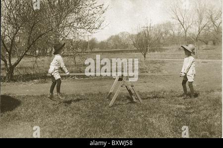 Two boys ride homemade sea saw in the field., circa 1900. USA. - Stock Photo