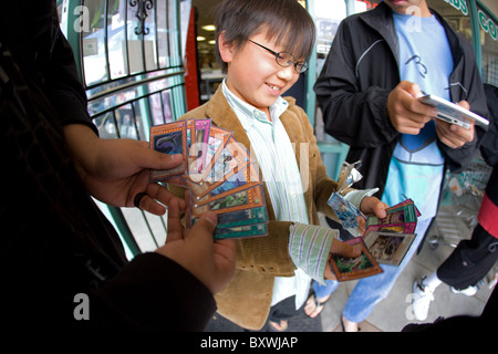 Happy Japanese boy looking at new Yugioh trading cards and showing them to friends. - Stock Photo
