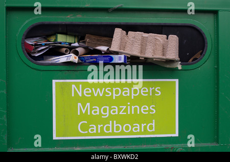 overloaded recycling facilities where people dump refuse beside skips - Stock Photo