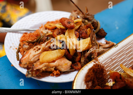 Grilled chicken, fried potato, and fried plantain is staple fare in Burkina Faso and throughout West Africa. - Stock Photo
