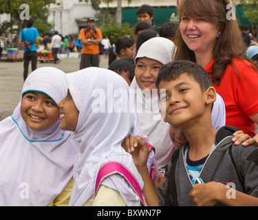 Group of Indonesian school children enjoying a day out at the historic Jakarta History Museum, Girls wearing their - Stock Photo