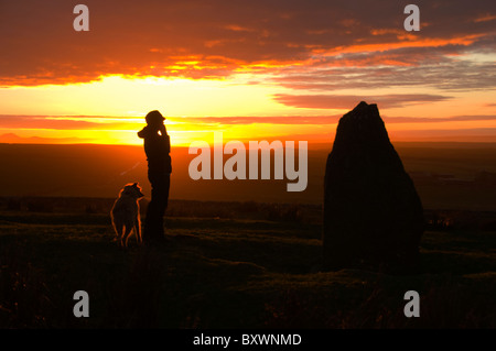 Young woman with dog by the standing stone on the Hill of Rigifa' at sunset.  Near Mey, Thurso, Caithness, Scotland, - Stock Photo