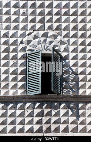 Geometric diamond facade with open shutters in Macerata in Le Marche Italy - Stock Photo
