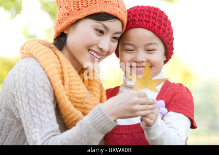 Mother and Daughter in a Park Looking at a Maple Leaf - Stock Photo