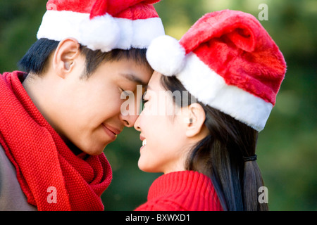 Young Couple Rub Noses while Wearing Santa Hats