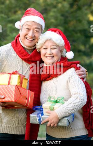 Senior Couple in Santa Hats Holding Christmas Gifts - Stock Photo