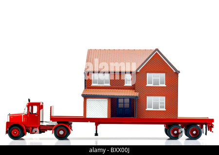 A flatbed articulated lorry loaded with a house isolated on a white background. Both are models. - Stock Photo