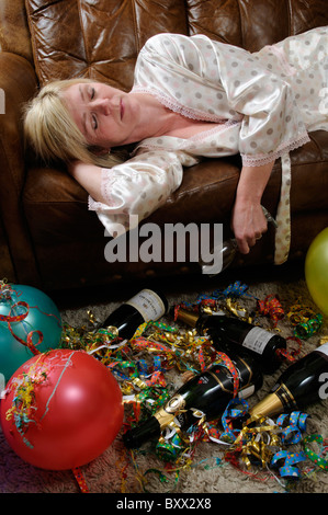 Woman holding an empty wine glass laying on a sofa and sleeping of a hangover - Stock Photo