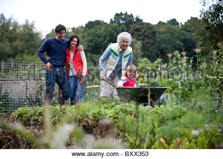 A grandmother pushing a young girl in a wheelbarrow on an allotment - Stock Photo