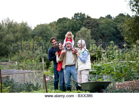 A family standing together on an allotment, laughing - Stock Photo
