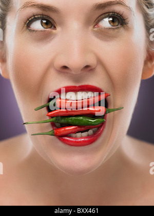 white blonde woman with chili's in her mouth - Stock Photo