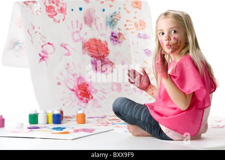 Cute little girl finger painting - Stock Photo