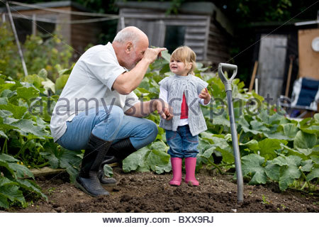 A grandfather showing a worm to his granddaughter on an allotment - Stock Photo