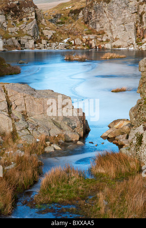 Iced over water in Foggin Tor Quarry during winter cold spell, Dartmoor, Devon UK - Stock Photo