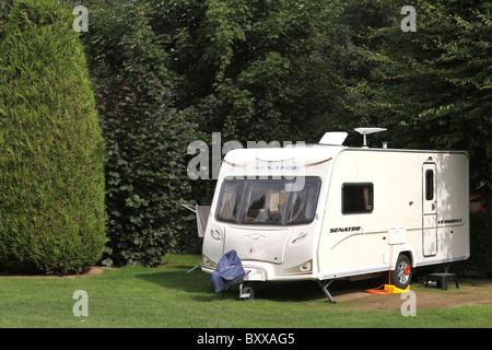 Touring trailer caravan pitched on a woodland caravan park - Stock Photo