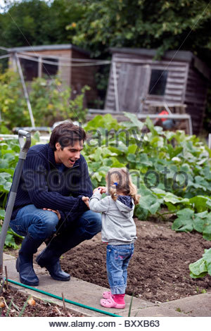 A father and daughter working on an allotment together - Stock Photo