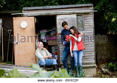A family having a break on an allotment, drinking tea - Stock Photo