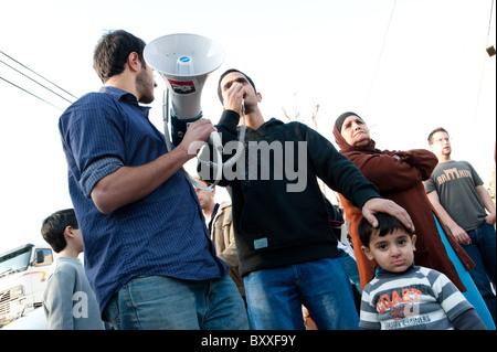 Israeli and Palestinian activists stand side by side during a weekly protest against Jewish settlements in East - Stock Photo