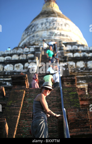 A tourist climbs the Shwesandaw Pagoda or temple AKA sunset temple in, Bagan Archaeological Zone, Myanmar. Burma - Stock Photo
