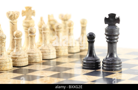Loyalty to the King - A pawn and his king face off against the entire army of opposing chess pieces. - Stock Photo