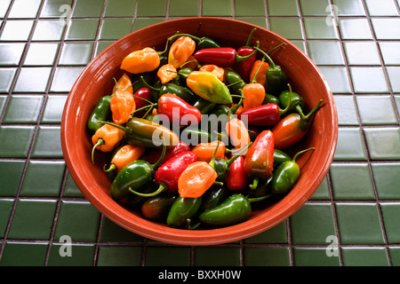 Bowl of Habanero and Jalapeno chili peppers on tile counter top - Stock Photo