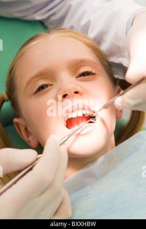 Close-up of little girl opening her mouth for dental checkup in stomatological office - Stock Photo