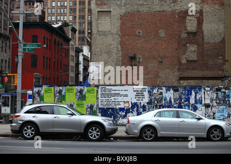 Cars parking next to a wall covered with posters and advertisements on Sixth avenue in Chinatown, New York city, - Stock Photo