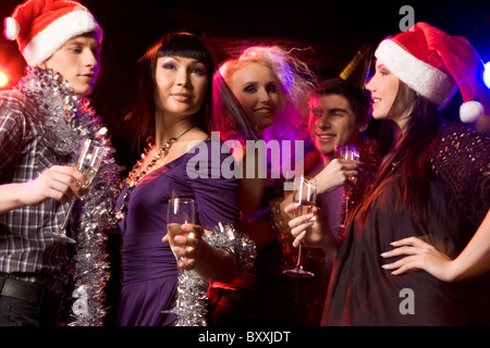 Happy friends with champagne dancing in night club during party