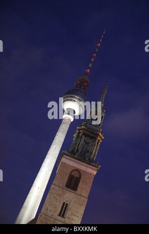 Fernsehturm or TV television tower beside the bell tower of historic St Marys Church or Marienkirche at nigh in - Stock Photo