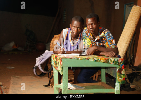 Two junior high school students (equivalent of the 7th grade in the US) study at night in the yard of their home. - Stock Photo