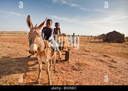 Two Fulani children return to the village of Jolooga in northern Burkina Faso after collecting water from a nearby - Stock Photo